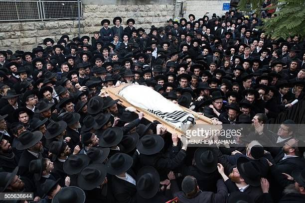 TOPSHOT Ultraorthodox Jews carry the body of Rabbi Refoel Shmulevitz wrapped in a prayer shawl during his funeral outside the Mir Yeshiva religious...