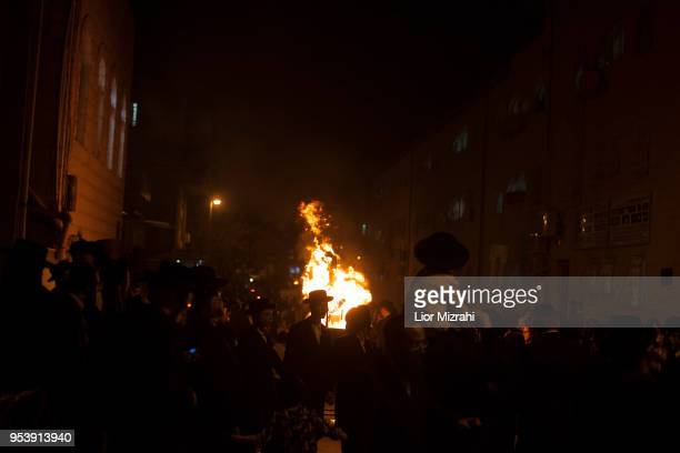 UltraOrthodox Jews dance next to a bonfire at Lag BaOmer celebration on May 2 2018 in Jerusalem Israel The Lag BaOmer bonfire is lit to commemorate...