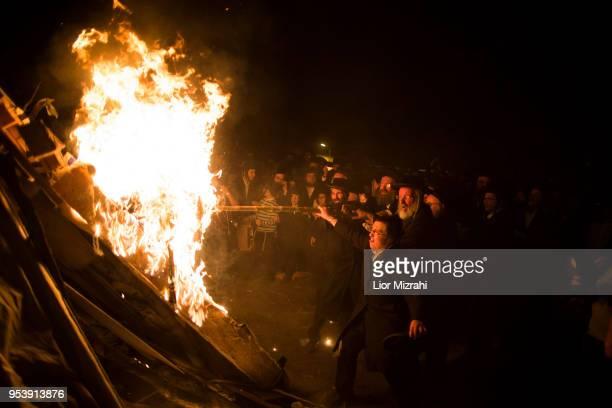 UltraOrthodox Jews hold a burning stick to light a bonfire for Lag BaOmer celebration on May 2 2018 in Jerusalem Israel The Lag BaOmer bonfire is lit...