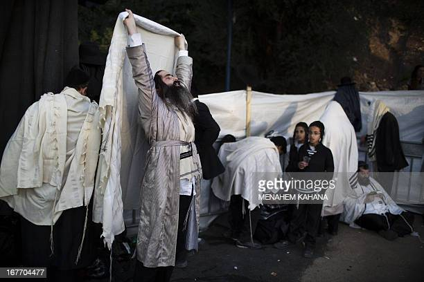 UltraOrthodox Jews pray during a ceremony at the grave site of Rabbi Shimon Bar Yochai in the northern Israeli village of Meron on April 28 2013 at...