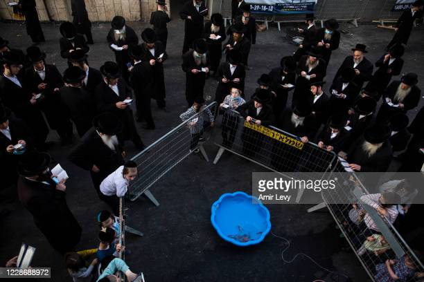 UltraOrthodox Jews pray near a kids pool tub as they praricipate in a Tashlich ceremony a head of Day of Atonement Yom Kippur which starts at Sunday...