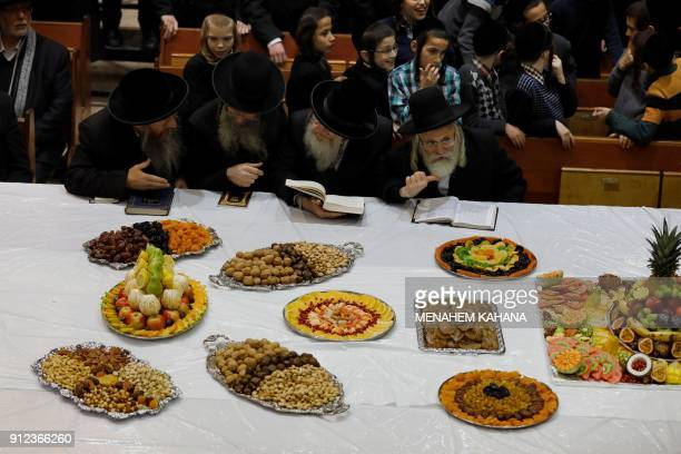 """Ultra-Orthodox Jews receive fruits during the celebration of the feast of """"Tu Bishvat"""" as they eat the fruits of the year with their Rabi at their..."""