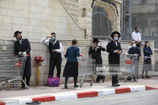 UltraOrthodox Jews some wearing protective masks queue for shopping in the religious Israeli city of Bnei Brak near Tel Aviv on April 06 2020 during...