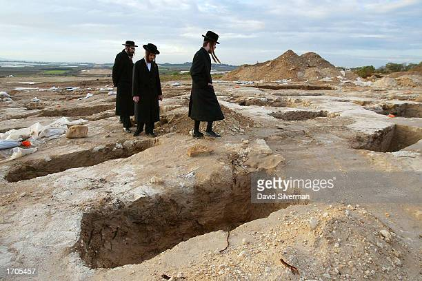 UltraOrthodox Jews walk amidst emptied graves as they protest against archeological excavations in an ancient cemetery December 31 2002 near Barkai...