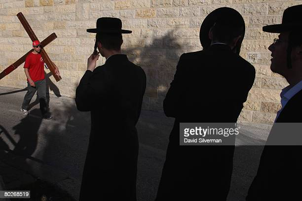 UltraOrthodox Jews watch Clive Cornish a 41yearold Christian pilgrim from Cardiff Wales carry his large wooden Crucifix as he retraces the footsteps...