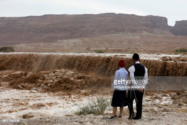Ultraorthodox Jews watch flooded water running through a valley blocking the main road along the Dead Sea in the Judean desert near the desert...