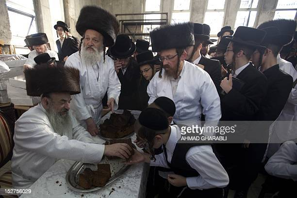 UltraOrthodox Jews wear white holiday cloths and eat cake during noon prayers a few hours before the start of Yom Kippur the Jewish holy day of...