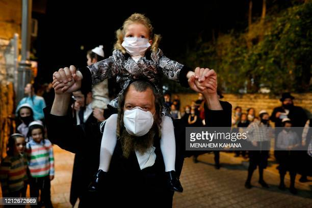 UltraOrthodox Jews wearing masks against the Covid19 coronavirus gather for a Lag BaOmer bonfire in Jerusalem's religious Mea Shearim neighbourhood...
