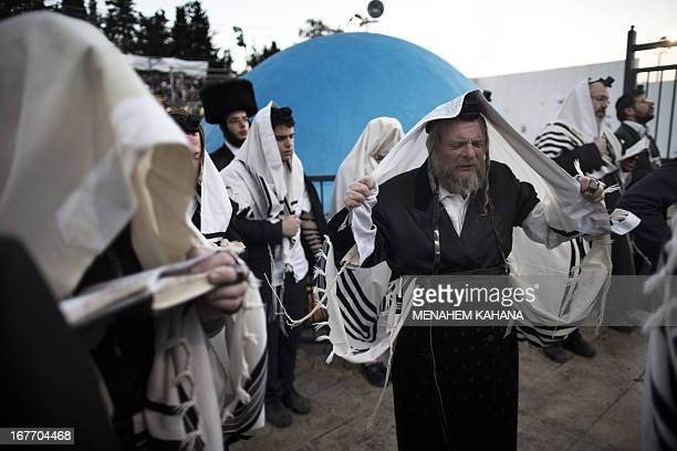 UltraOrthodox Jews wearing tallits and tefillins pray during a ceremony at the grave site of Rabbi Shimon Bar Yochai in the northern Israeli village...