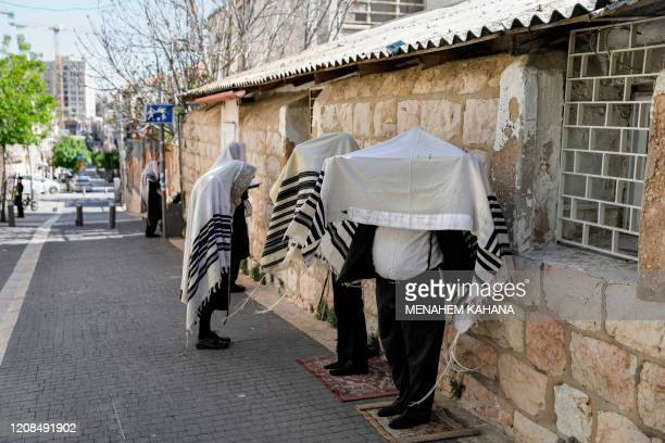 UltraOrthodox Jews wearing the traditional Tallit Jewish prayer shawls pray along a street outside their closed synagogue in Jerusalem on March 29...