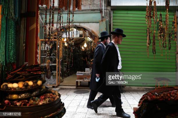 UltraOrthodox men walk past shops in Jerusalem's Old City on May 23 after the easing of lockdown measures put in place to combat the threat of the...