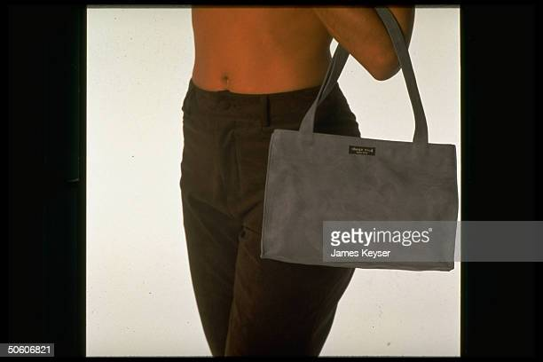 Ultrasuede pantsclad model carrying faux suede handbag by designer Kate Spade re synthetic's revival in fall fashions