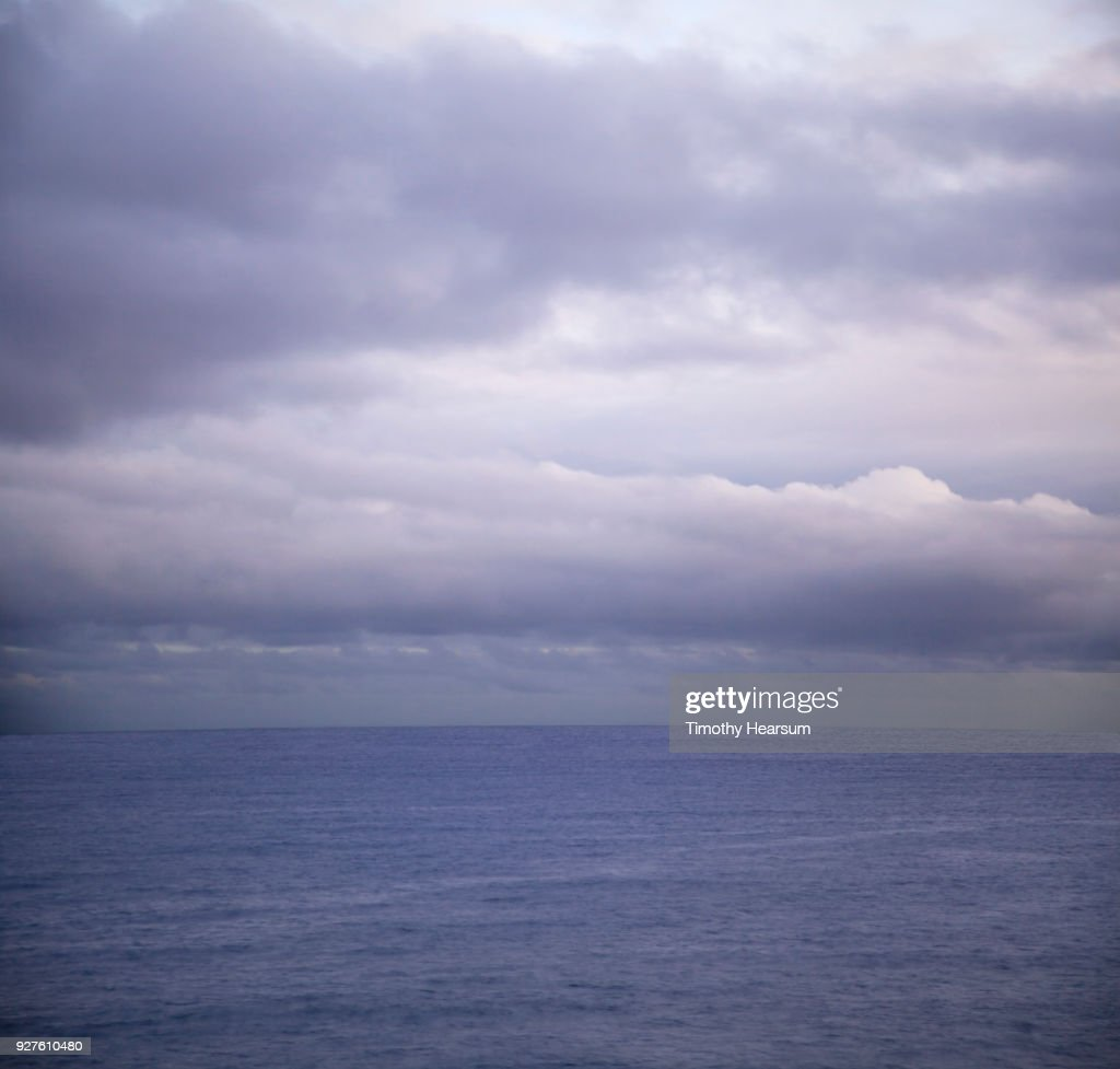 Ultraviolet sky and clouds creating a matching colored ocean : Stock Photo