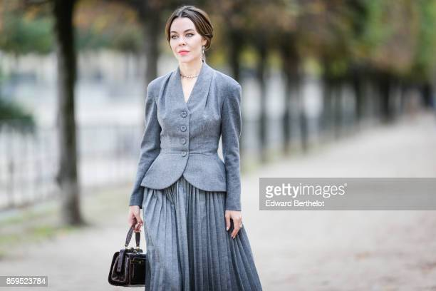 Ulyana Sergeenko is seen wearing a gray blazer jacket a gray pleated skirt a black leather bag at the Tuileries garden on October 7 2017 in Paris...