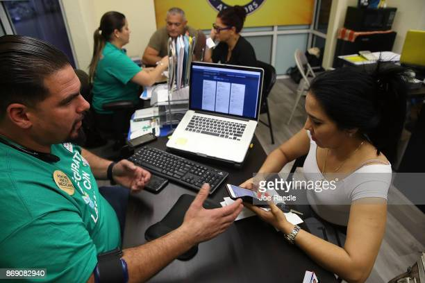 Ulysses Hernandez an insurance agent from Sunshine Life and Health Advisors speaks with Yuricel Duran as she shops for insurance under the Affordable...