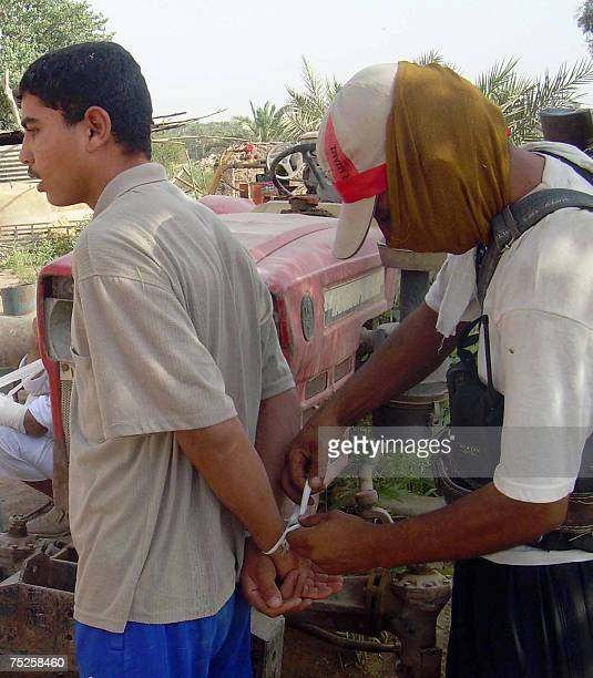 A local Sunni militiaman who decided to fight AlQaeda ties the hands of a suspect whom he has arrested 07 July 2007 during a raid in Um AlIzam...