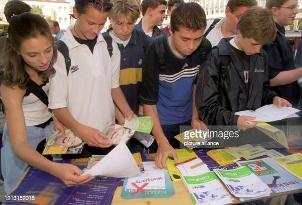 """Um einen Tisch mit Informationsmaterialien der Parteien drängen sich Jugendliche am 23.8.1999 in Düsseldorf. Unter dem Slogan """"Erstmal Kommunalwahl..."""