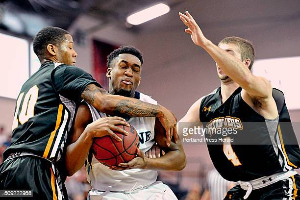 UMaine's Aaron Calixte is fouled by University of MarylandBaltimore County Jairus Lyles as fellow UMBC teammate Joel Wincowski at right closes in...
