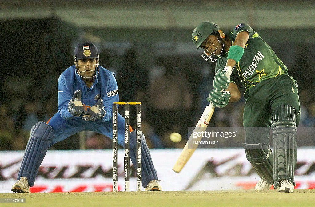 Umar Akmal of Pakistan hits a four over extra cover with MS Dhoni of India looking on during the 2011 ICC World Cup second SemiFinal between Pakistan.