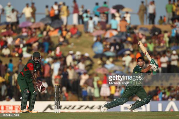 Umar Akmal of Pakistan hits to the offside as wicketkeeper Morris Ouma looks on during the Kenya v Pakistan 2011 ICC World Cup Group A match at the...