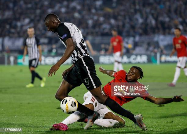 Umar Sadiq of Partizan is challenged by Aaron WanBissaka of Manchester United during the UEFA Europa League group L match between Partizan and...