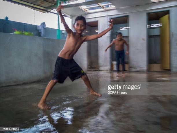 RAHMANIYAH KLANG SELANGOR MALAYSIA Umar seen sliding on a slippery floor with his feet while his friend Ali wait for his turn Umar is from Johor and...