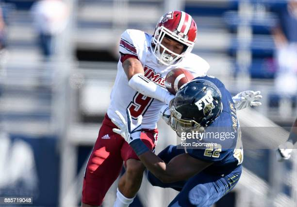 UMass defensive back Isaiah Rodgers takes the ball away from Florida International University running back Shawndarrius Phillips during an NCAA...