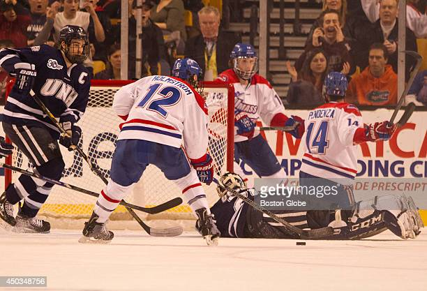 UMass Lowell River Hawks Josh Holmstom scores a goal with University of New Hampshire Wildcats goalie Casey DeSmith out of position and Eric Knodel...