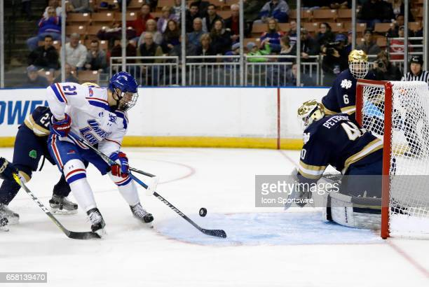 UMass Lowell River Hawks left wing Jake Kamrass can not get the handle on the puck in front of Notre Dame Fighting Irish goaltender Cal Petersen...