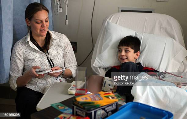 UMass Medical School student Meg Preissler plays a game with Jameson Laliberte while he receives dialysis for kidney cancer at the UMass Memorial...