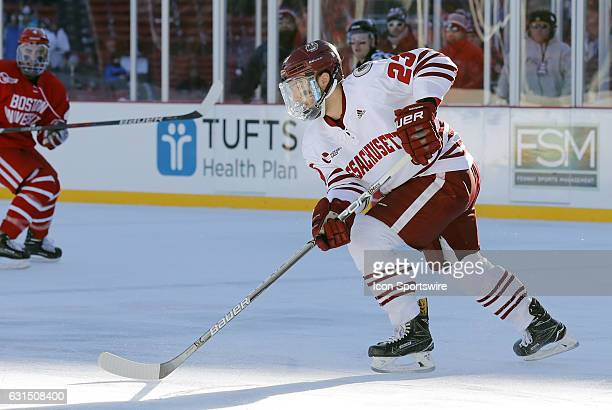 UMass Minutemen forward Jonny Lazarus brings the puck up ice during a Frozen Fenway NCAA Men's Division 1 hockey game between the Boston University...