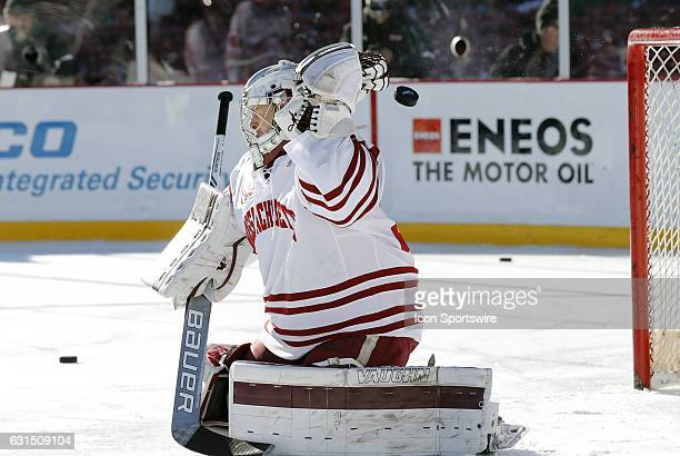 UMass Minutemen goaltender Alex Wakaluk knocks a puck over the goal during warm up before a Frozen Fenway NCAA Men's Division 1 hockey game between...