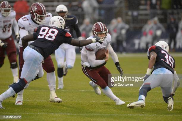 UMass Minutemen quarterback Andrew Ford attempts to split two UConn Defenders UConn Huskies defensive lineman Lwal Uguak and UConn Huskies defensive...