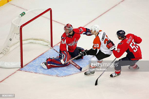 J Umberger of the Philadelphia Flyers scores the first goal of the game against Cristobal Huet and Jeff Schultz of the Washington Capitals during...
