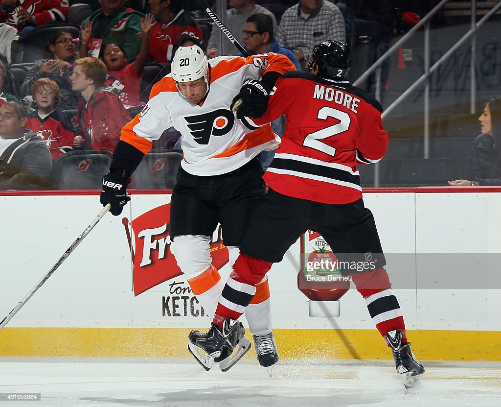 R.J. Umberger #20 of the Philadelphia Flyers steps into John Moore #2 of the New Jersey Devils during the third period at the Prudential Center on October 2, 2015 in Newark, New Jersey. The Devils defeated the Flyers 3-2 in the shootout.