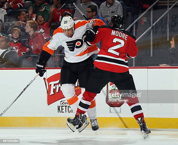 J Umberger of the Philadelphia Flyers steps into John Moore of the New Jersey Devils during the third period at the Prudential Center on October 2...