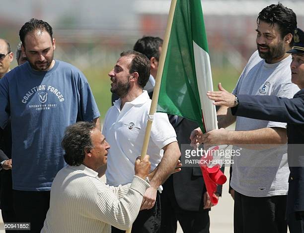 Umberto Cupertino who is greeted by his father Salvatore Stefio and Maurizio Agliana the three Italian hostages freed yesterday by coalition forces...