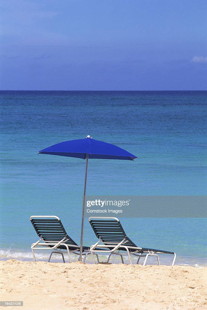 Umbrella and lounge chairs on beach : Stockfoto