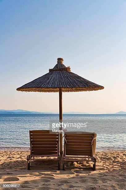 Umbrella and Sunchairs for two on beach