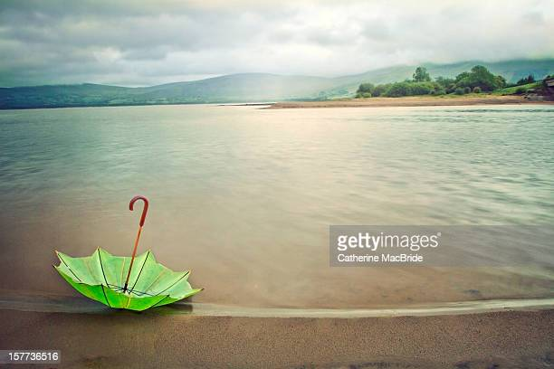 umbrella at lake edge - catherine macbride stock pictures, royalty-free photos & images
