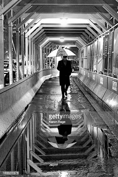 Umbrella carrying gentleman uses a covered construction passageway to avoid a heavy snow in Washington, DC. His image in reflected in a large puddle.
