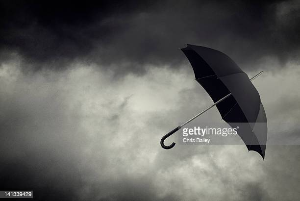 umbrella floating in stormy sky - ominous stock pictures, royalty-free photos & images