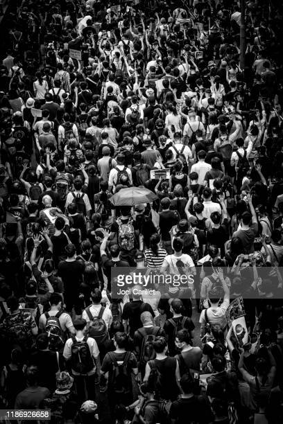 umbrella in a thick crowd of hong kongers - thick black woman stock photos and pictures