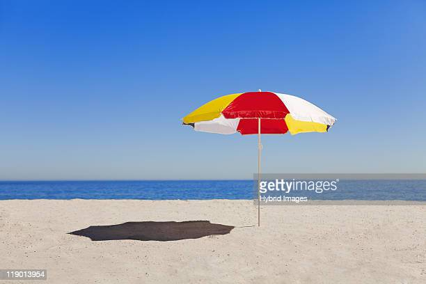 umbrella in sand on empty beach - sombrilla de playa fotografías e imágenes de stock