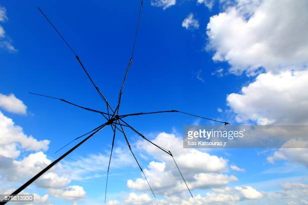 Umbrella skeleton against blue sky with fluffy clouds