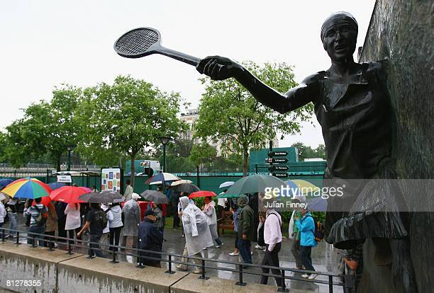 Umbrella wielding fans walk past a statue of former French tennis player, Suzanne Lenglen as rain halts play on day five of the French Open at Roland...