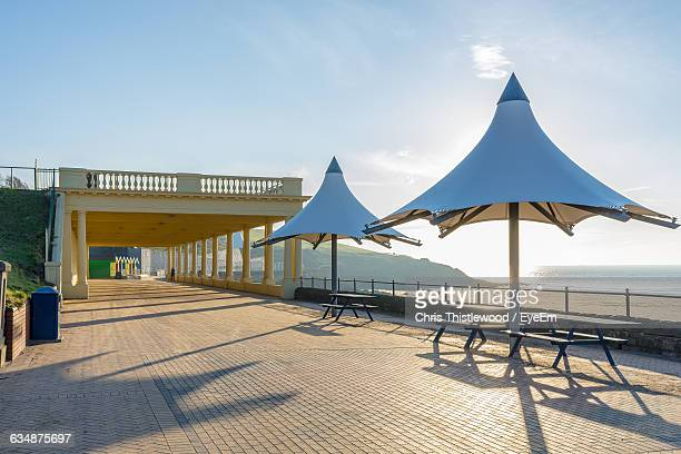 Umbrellas And Picnic Table By Beach Against Sky On Sunny Day