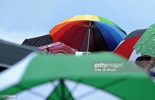 Umbrellas are pictured as tennis fans shelter from the rain on Court 2 during a game between Spanish player David Ferrer and Ryan Harrison of US in a...