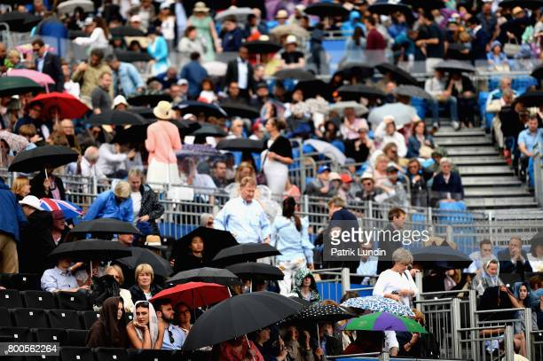 Umbrellas come out inside the stands as rain begins on day six of the 2017 Aegon Championships at Queens Club on June 24 2017 in London England