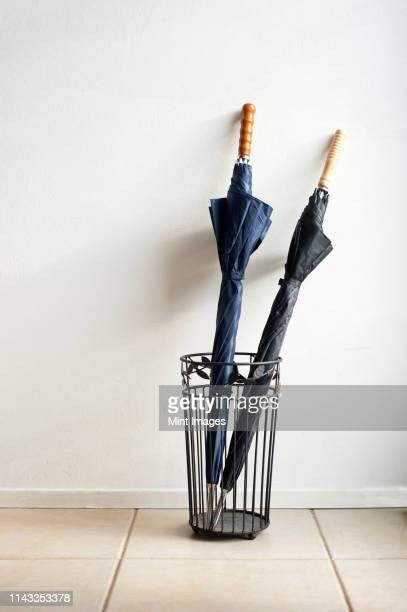 umbrellas in wire stand - umbrella stock pictures, royalty-free photos & images